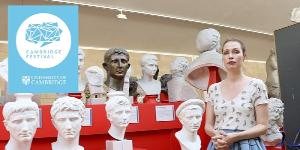 Curator Susanne Turner standing in front of plaster cast busts.